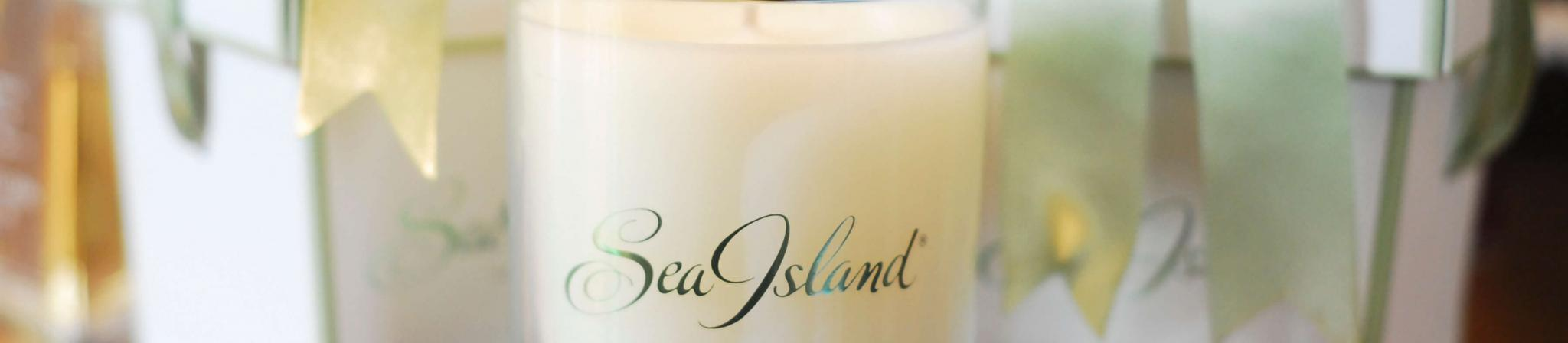 A Sea Island spa candle in between two gift boxes