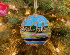 Magnified view of Sea Island christmas ornament hanging on lit up christmas tree